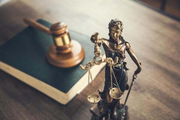 Houten rechter op boek met justitie dame op bureau