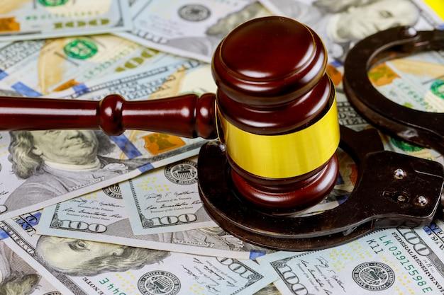 Houten rechtershamer met handcuffs op mening van honderd dollarsrekeningen voor het gerecht