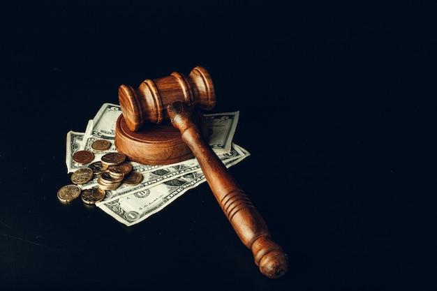 Houten rechtershamer op de close-up van amerikaanse dollarbankbiljetten. justitie corruptie concept