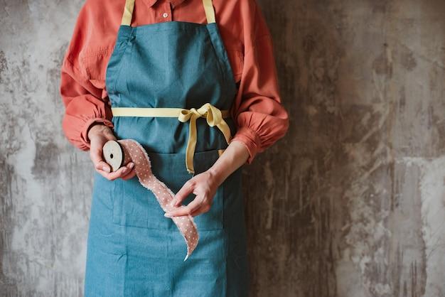 Houten retro haspel met roze polka dot vlecht in de handen van een naaister in een schort