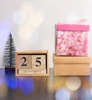 Houten retro kalender van blokken, decoratieve kerstboom en kartonnen dozen met geschenken
