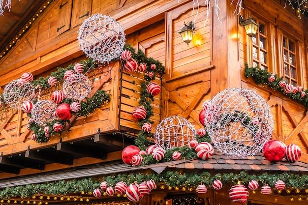 Houten retro restaurantgebouw versierd met kunstmatige dennenboom met slinger en veel rode en witte kerstballen op winterdag, geen sneeuw.