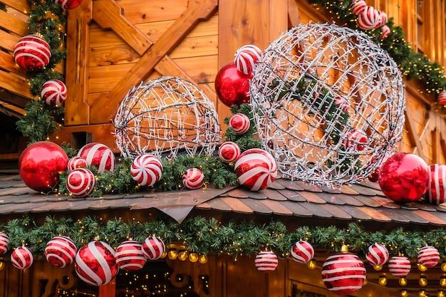 Houten retro restaurantgebouw versierd met kunstmatige dennenboom met slinger en veel rode en witte kerstballen