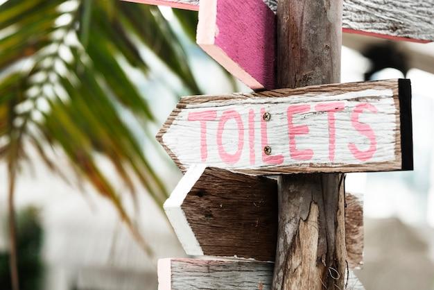 Houten richtingaanwijzers naar de toiletten