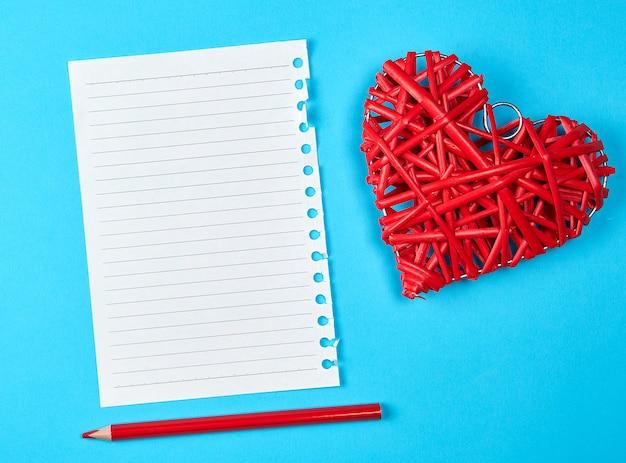 Houten rieten rood hart en een leeg wit blad van blocnote