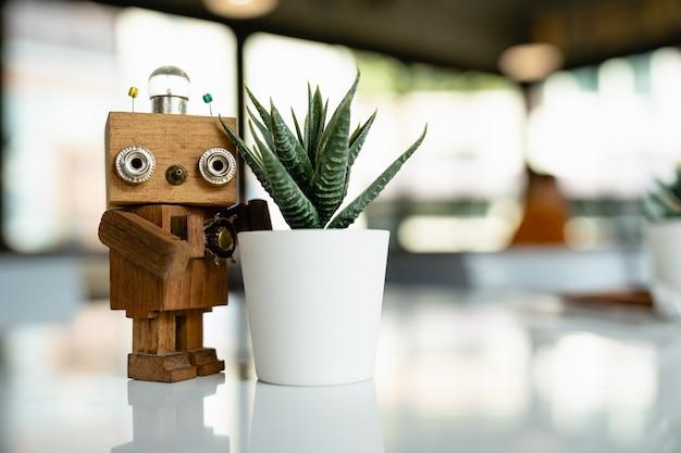 Houten robot met cactus op witte tafel