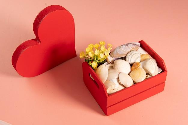 Houten rode doos met schelpen en bloemen met een vormhart dat de zomer en liefde symboliseert op een lichtrode achtergrond