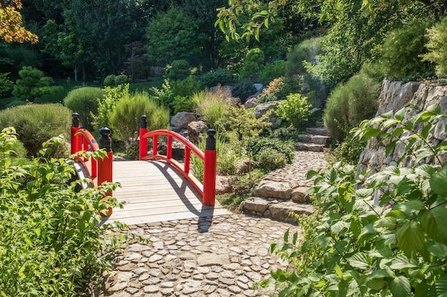 Houten rode voetbrug bij japanse tuin in de zomer