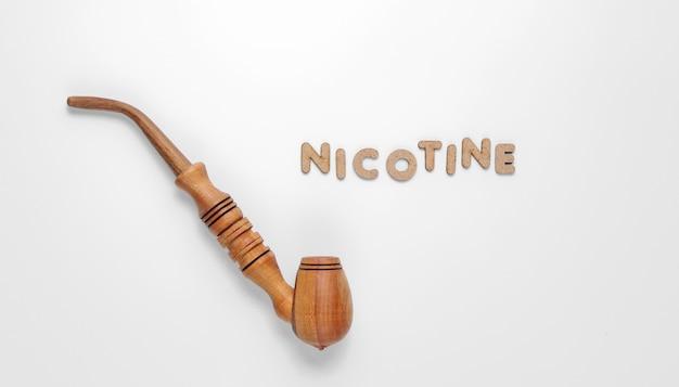 Houten rookpijp met het woord nicotine van houten letters