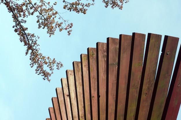 Houten rooster met blauwe lucht en bladerenachtergrond