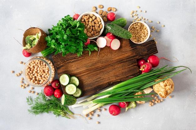 Houten rustieke snijplank met ingrediënten voor het koken van veganistisch eten op lichte achtergrond bovenaanzicht
