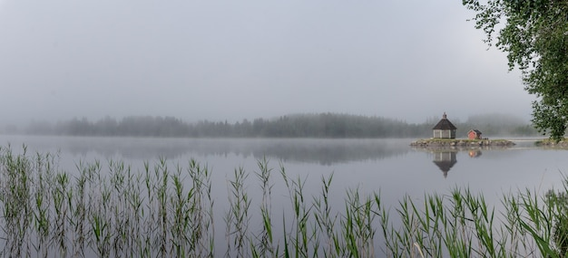 Houten sauna in de mist in de vroege ochtend op het meer gaxsjon, zweden