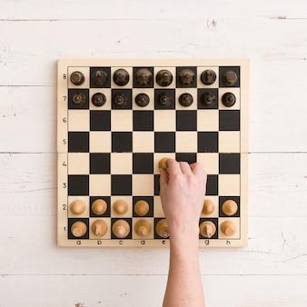 Houten schaakbord met figuren klaar voor het spel en mans hand die zijn eerste schaakzet maakt