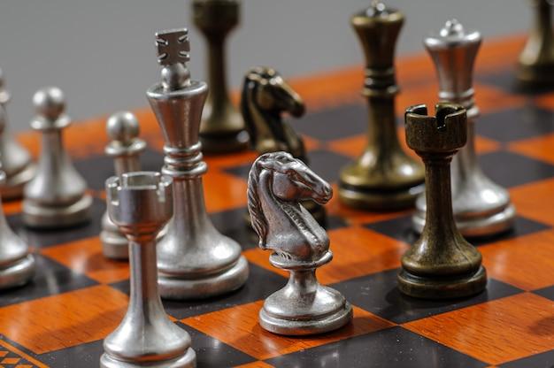 Houten schaakbord met metalen stukken. schaakmat.