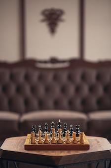 Houten schaakstukken op een bordspel, op een houten veelhoekige vintage tafel, verticale oriëntatie, selectieve focus met kopieerruimte.