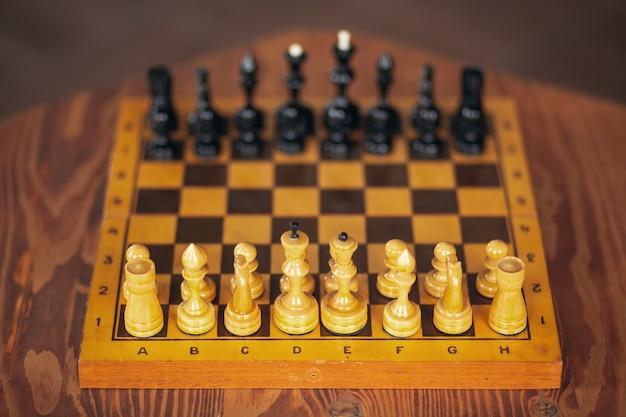 Houten schaakstukken op een bordspel, op vintage tafel, selectieve aandacht.