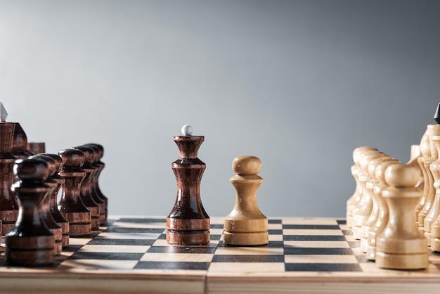Houten schaakstukken op een schaakbord, de confrontatie van de witte pion en de zwarte koningin, planning en besluitvorming