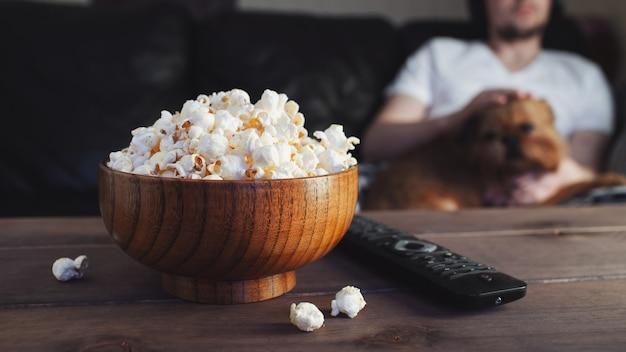 Houten schaal met gezouten popcorn en tv-afstandsbediening.