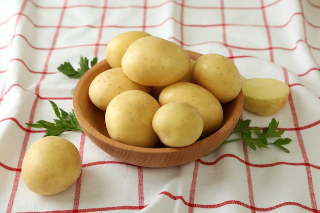 Houten schaal met jonge aardappel op tafelkleed