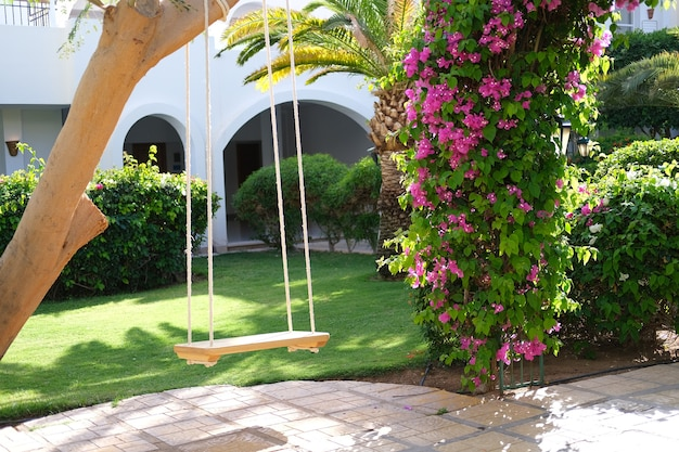 Houten schommel in de groene tuin omringd door bloemen en palmen foto van hoge kwaliteit