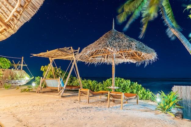 Houten schommel met een matras onder een baldakijn en stroparaplu op het tropische strand in de buurt van zee 's nachts, eiland zanzibar, tanzania, oost-afrika, reis- en vakantieconcept