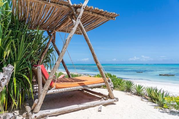 Houten schommel met een matras onder een baldakijn op het tropische strand in de buurt van zee, eiland zanzibar, tanzania, oost-afrika, reis- en vakantieconcept