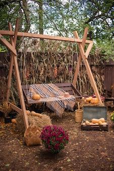Houten schommel met pompoenen voor halloween in de herfst in de tuin bij het huis