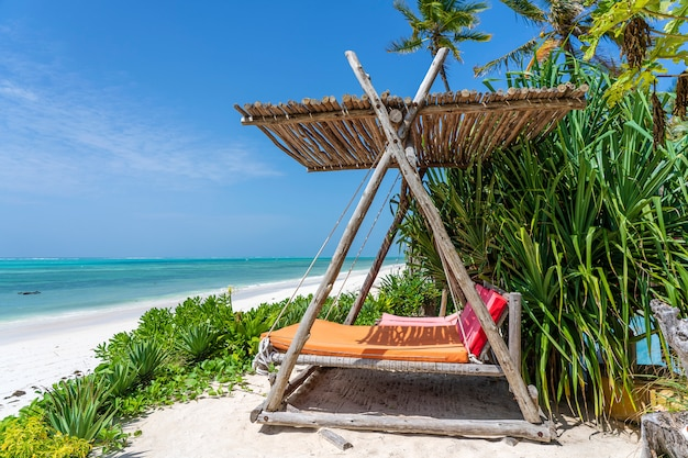 Houten schommel onder een luifel op het tropische strand in de buurt van de zee
