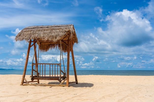 Houten schommel onder een rieten dak op een tropische zandstrand in de buurt van de zee op het eiland phu quoc, vietnam. reizen en natuur concept