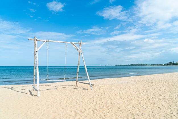 Houten schommel op het strand met zee strand achtergrond