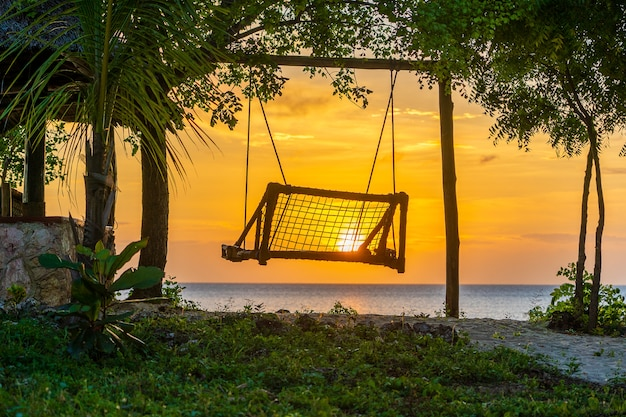Houten schommel van prachtige zonsondergang op het eiland zanzibar