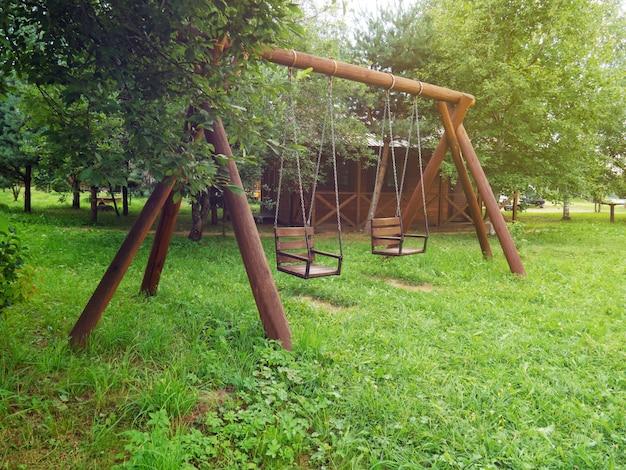 Houten schommel voor twee voor de recreatie van kinderen, ontspannen in de natuur. ruimte kopiëren.