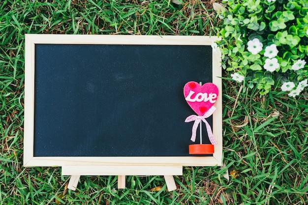 Houten schoolbord en bloempot in vierkante vorm op groen gras