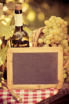 Houten schoolbordspatie, wijnfles en druiven van wijnstok in de herfst