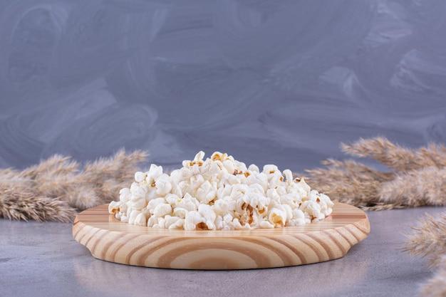 Houten schotel met een portie popcorn in het midden van gedroogd naaldgras op marmeren achtergrond. hoge kwaliteit foto