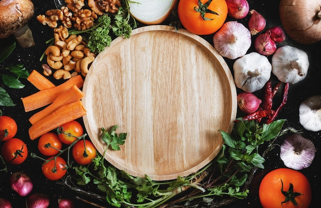 Houten schotel omringen met vers gezond voedsel op zwart hout