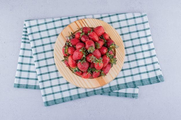 Houten schotel op een gevouwen tafelkleed met een stapel aardbeien op marmeren achtergrond.