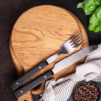 Houten serveerplank en bestek vork en mes nul afval maaltijd op tafel kopieer ruimte eten