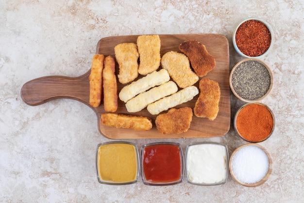 Houten snackbord met rondom kipnuggets, kaasstengels, gegrilde worstjes en sauzen.