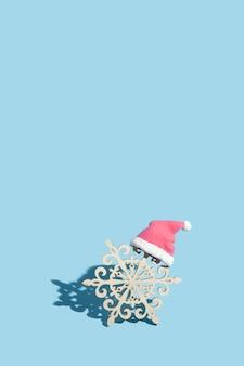 Houten sneeuwvlok in kerstmuts op blauwe achtergrond: nieuwjaar minimaal concept