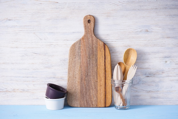 Houten snijplank en keukengerei op houten tafel, plaats voor tekst.