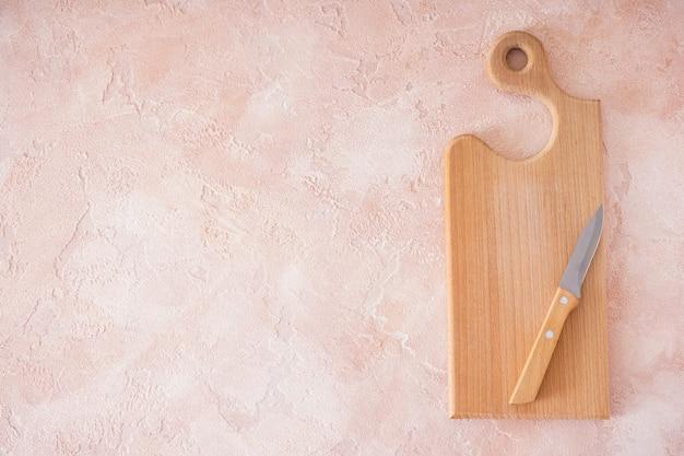Houten snijplank en mes op beige achtergrond, ruimte voor tekst. plat leggen.