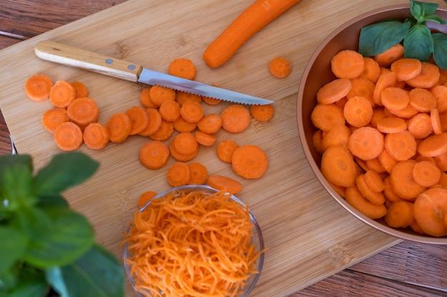 Houten snijplank en verse rauwe wortelen in verschillende vorm - gezond, dieet, groenten concept