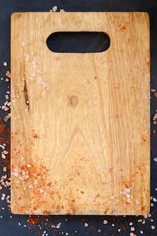 Houten snijplank en vlokken zout en rode peper. voedselkeuken koken en culinair procesconcept