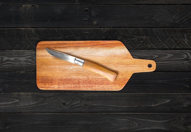 Houten snijplank en zakmes op zwarte houten tafel achtergrond
