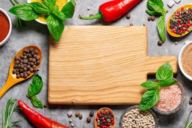 Houten snijplank met heldere aromatische kruiden en specerijen bovenaanzicht op betonnen achtergrond
