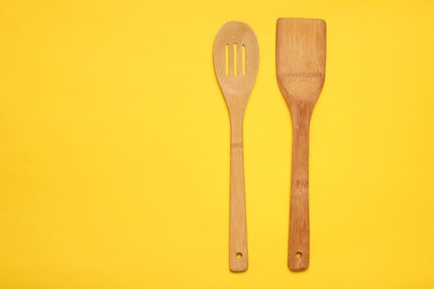 Houten spatel voor het koken op een gele tafel. keukenconcept, minimalisme