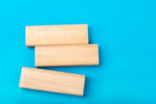 Houten spaties op een blauwe achtergrond. een plaats voor inscriptie van uw bericht. creatieve messenger.houten blokken met textuur uit het spel django