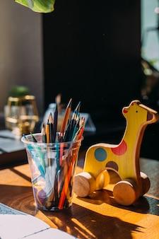 Houten speelgoed giraffe kleurpotloden en een kleurboek op een houten tafel