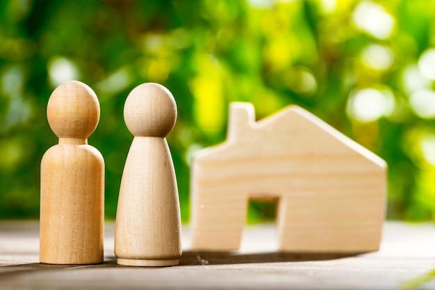 Houten speelgoed huis en houten familie op gebladerte close-up